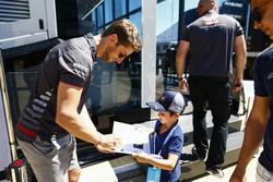 Romain Grosjean, Haas F1 Team, signs an autograph for a young fan