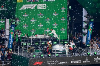 Lewis Hamilton, Mercedes AMG F1, 1st position, waves a Mexican flag from the podium