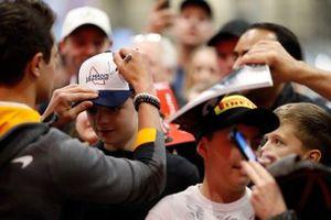 Lando Norris, McLaren signs a cap for a fan
