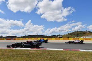 Lewis Hamilton, Mercedes W12, passes Nicholas Latifi, Williams FW43B, and Nikita Mazepin, Haas VF-21