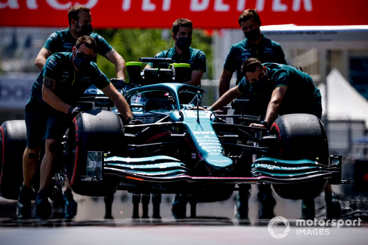 Los mecánicos mueven el coche de Lance Stroll, Aston Martin AMR21