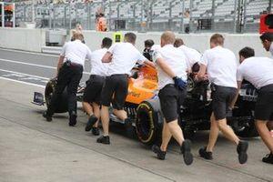 McLaren MCL34 siendo empujado por miembros del equipo