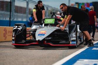 Mechanics push Oliver Rowland's, Nissan e.Dams, Nissan IMO1 through the pit lane