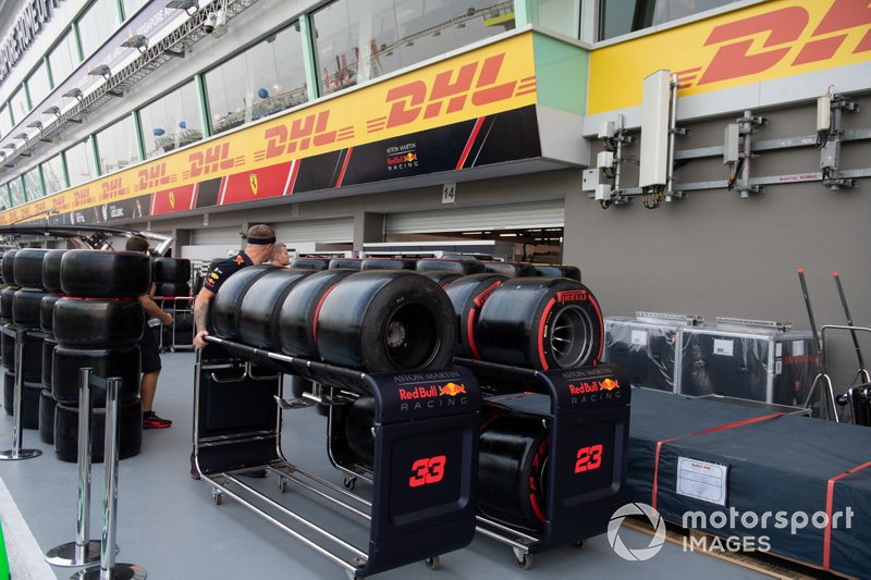 Pirelli tyres allocated to Red Bull are pushed on a trolley through the pit lane