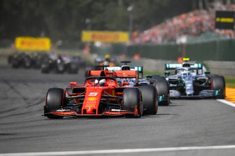 Sebastian Vettel, Ferrari SF90, leads Lewis Hamilton, Mercedes AMG F1 W10, Valtteri Bottas, Mercedes AMG W10, and the remainder of the field on the opening lap