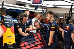 Red Bull mechanics work on a front wing
