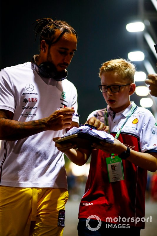 Lewis Hamilton, Mercedes AMG F1, signs an autograph for a young fan