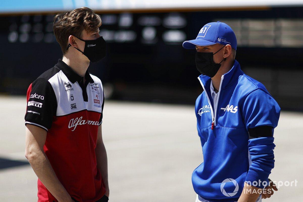 Callum Ilott, piloto de pruebas y reserva de Alfa Romeo Racing habla con Mick Schumacher, Haas F1 en el paddock
