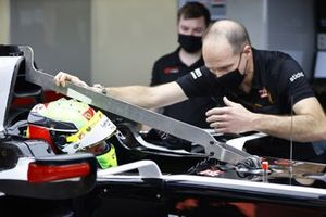 Mick Schumacher sits in his Haas VF-20 for his seat fitting with race engineer Gary Gannon