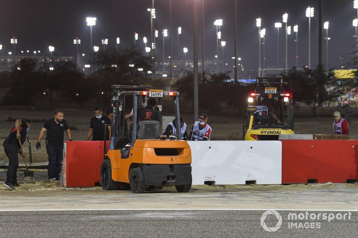 Un equipo de reparación reconstruye las barreras tras el accidente de la primera vuelta