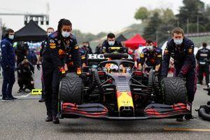 Los mecánicos empujan el coche de Sergio Pérez, Red Bull Racing RB16B, en la parrilla