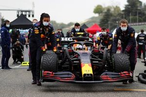 Mechanics push the car of Sergio Perez, Red Bull Racing RB16B, on the grid