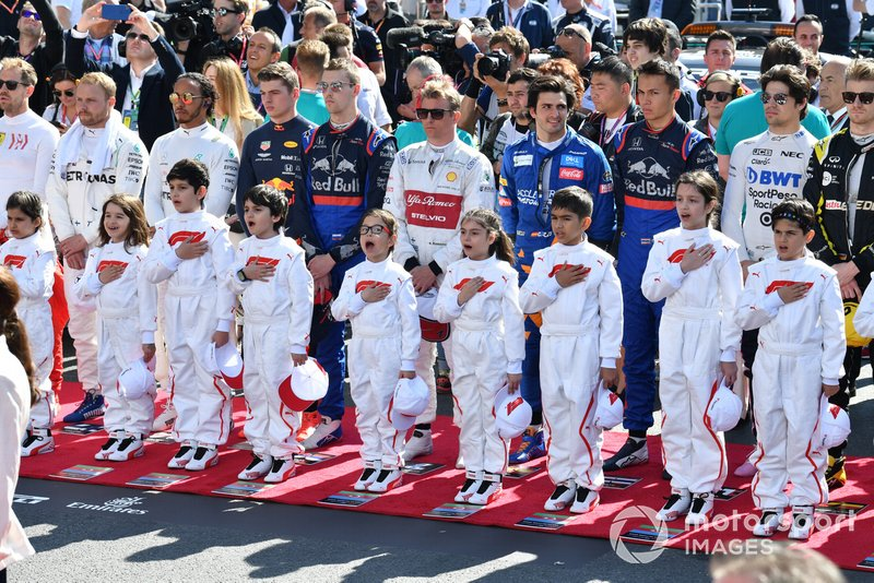 The drivers and Grid Kids stand for the national anthem prior to the start