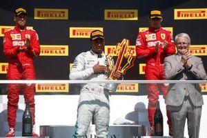 Sebastian Vettel, Ferrari, seconda posizione, Lewis Hamilton, Mercedes AMG F1, prima posizione, con il suo trofeo, e Charles Leclerc, Ferrari, terza posizione, sul podio