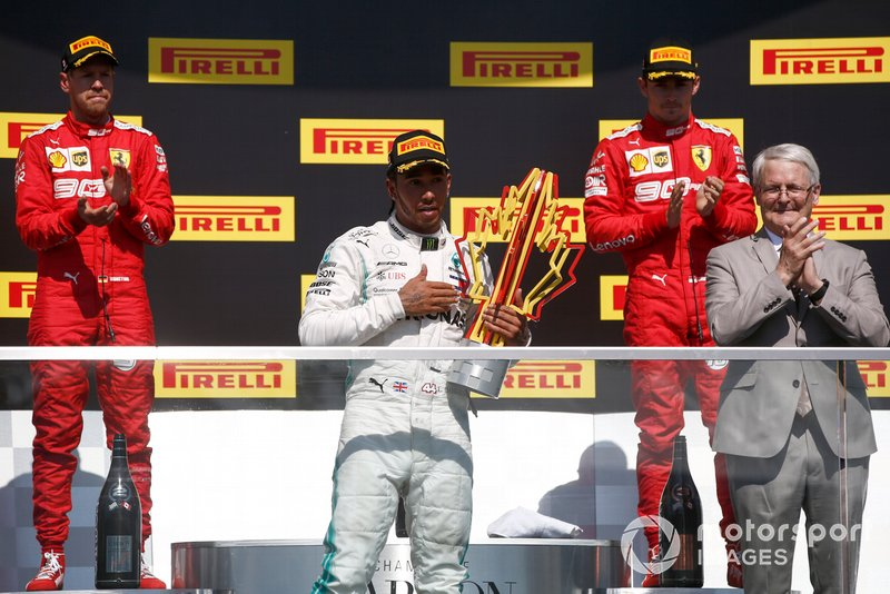 Sebastian Vettel, Ferrari, 2nd position, Lewis Hamilton, Mercedes AMG F1, 1st position, with his trophy, and Charles Leclerc, Ferrari, 3rd position, on the podium