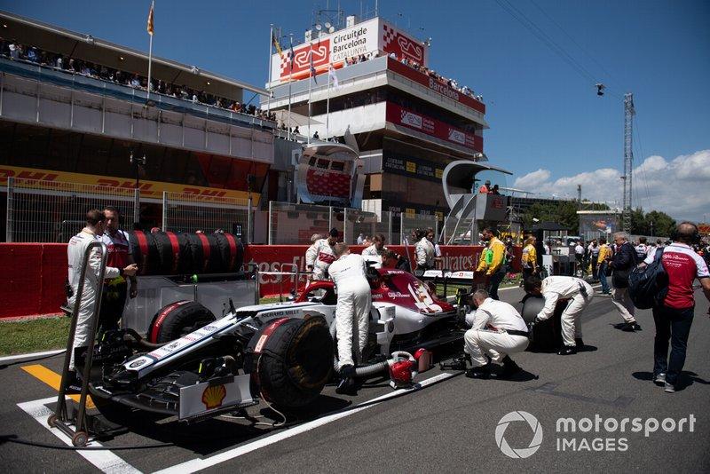 Des mécaniciens sur la grille avec la voiture de Kimi Raikkonen, Alfa Romeo Racing C38