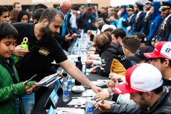 Fans line up to get autographs from the drivers