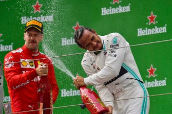 Sebastian Vettel, Ferrari, 3rd position, and Lewis Hamilton, Mercedes AMG F1, 1st position, celebrate with Champagne on the podium