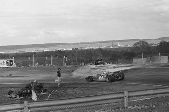 Jack Brabham, Brabham BT33 passes the burnt out wrecks of Jacky Ickx's Ferrari, left and Jackie Oliver's BRM