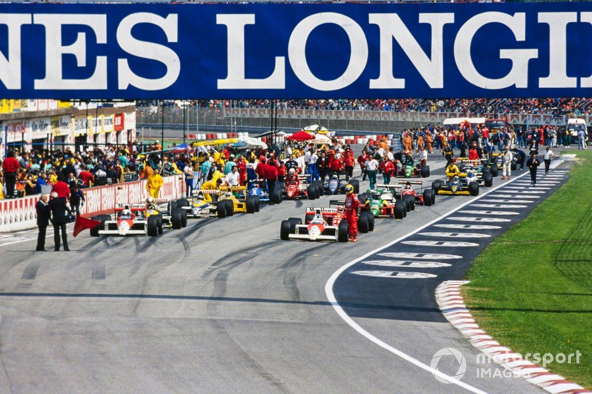Los monoplazas alineados en la parrilla durante el período de bandera roja. Ayrton Senna de pie junto a su McLaren MP4-5 Honda