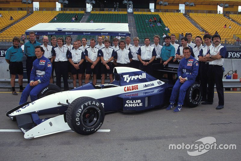 Olivier Grouillard sits on a front wheel of his Tyrrell 020B Ilmor with Andrea de Cesaris and the team members
