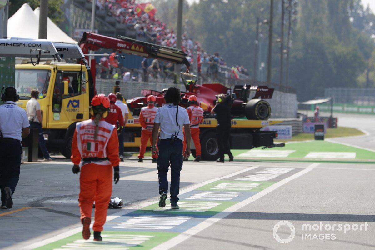 Los comisarios con el coche accidentado de Carlos Sainz Jr., Ferrari SF21