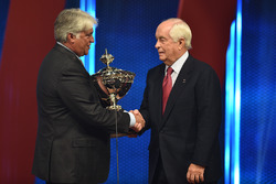 Roger Penske receives the champion's trophy from IndyCar CEO Mark Miles