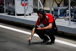 Un mécanicien Arden International prend la température de la piste