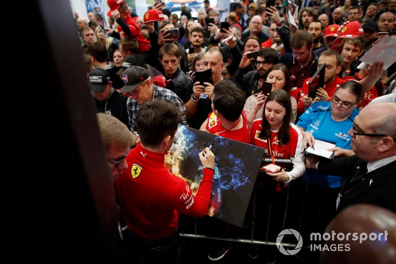Charles Leclerc, Ferrari signs a canvas for a fan in front of the Autosport stage