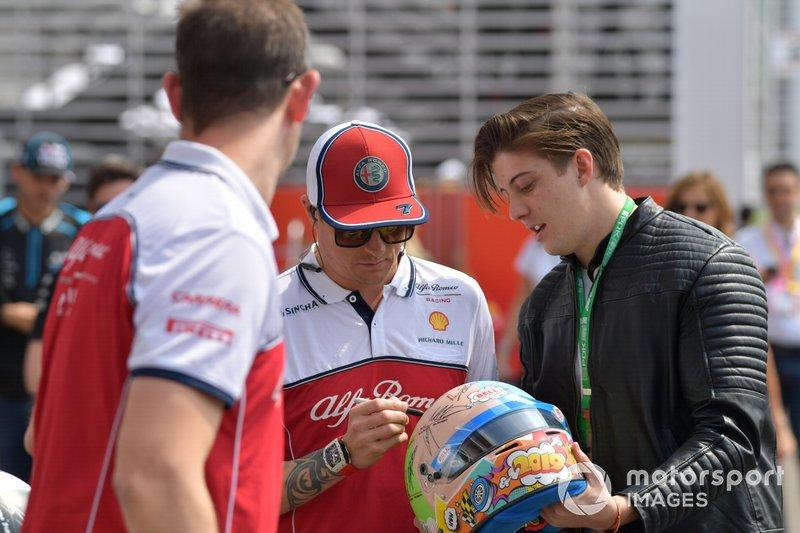 Kimi Raikkonen, Alfa Romeo Racing, signs a crash helmet