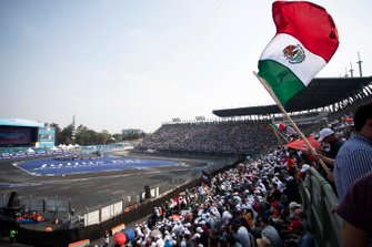 A fan waves the Mexican flag in the grandstand
