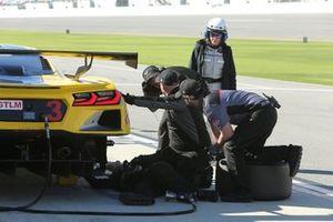 Corvette Racing crew members work on the rear suspension