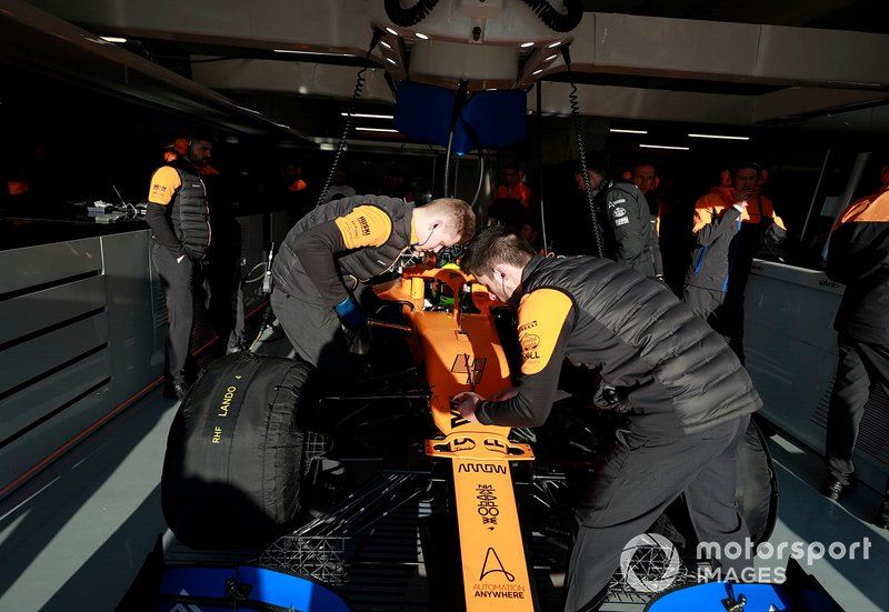Lando Norris, McLaren MCL35 in thee garage with mechanics