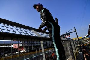 Pole man Lewis Hamilton, Mercedes, climbs the catch fence in celebration after securing pole