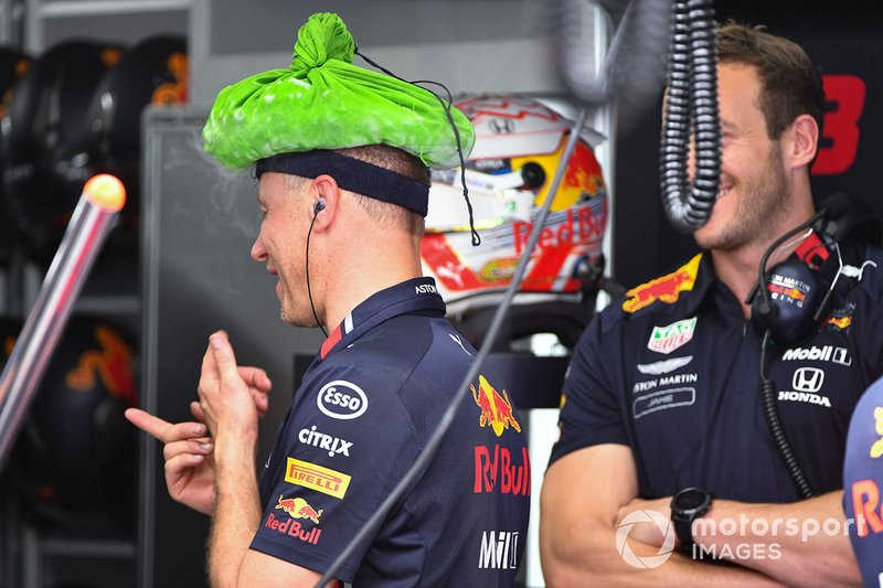 A Red Bull mechanic with a cooling device on his head