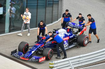 The Daniil Kvyat Toro Rosso STR14 is pushed into the pit lane