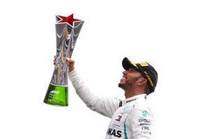 Lewis Hamilton, Mercedes AMG F1, fête sa victoire sur le podium en soulevant le trophée du vainqueur