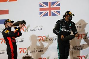 Max Verstappen, Red Bull Racing, 2nd position, and Lewis Hamilton, Mercedes-AMG F1, 1st position, celebrate with Champagne on the podium