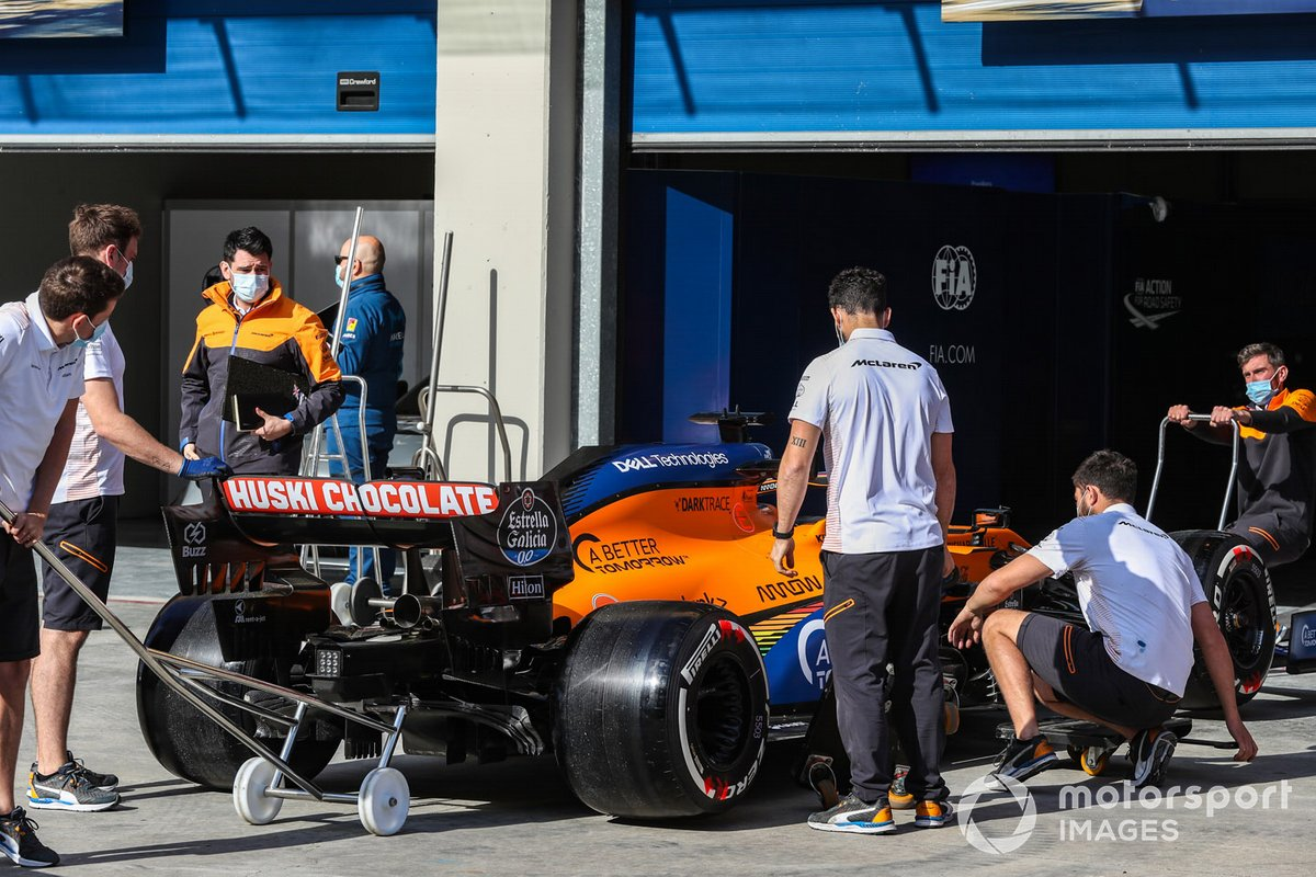 McLaren personnel with one of their cars outside the garage