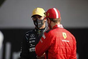 Lewis Hamilton, Mercedes-AMG F1, talks to Sebastian Vettel, Ferrari, on the grid for the end of season photo