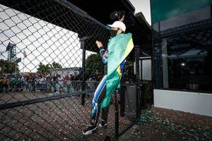 Winner #10 Wayne Taylor Racing Acura ARX-05 Acura DPi: Helio Castroneves climbs the fence as the fans cheer him on