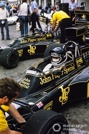 Jacky Ickx and Ronnie Peterson sit in their Lotus 72E Fords in the pits