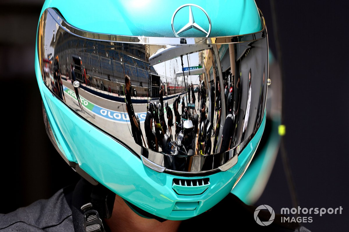 Il pit stop della Mercedes riflette sulla visiera del casco di un meccanico
