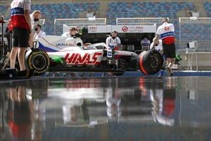 Haas F1 team engineers in the garage and Mick Schumacher, Haas VF-21