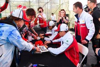 Kimi Raikkonen, Alfa Romeo Racing and Antonio Giovinazzi, Alfa Romeo Racing sign autographs for fans