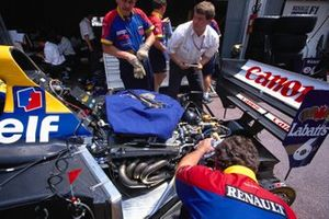 Mechanics work on a Williams FW14B Renault in the pits