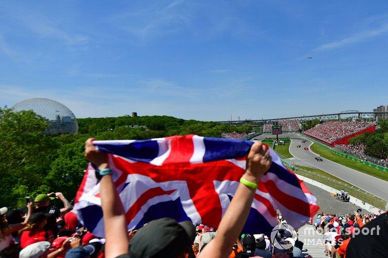 Un fan ondea la bandera de Reino Unido mientras Lewis Hamilton, Mercedes AMG F1 W10, lidera por delante de Charles Leclerc, Ferrari SF90, Daniel Ricciardo, Renault R.S.19, y el resto de la parrilla