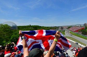 Un fan agite un Union Jack devant Lewis Hamilton, Mercedes AMG F1 W10, Charles Leclerc, Ferrari SF90, Daniel Ricciardo, Renault R.S.19, et le reste du peloton