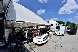Crews work on the #4 TA Ford Mustang driven by Paul Fix of Ave Racing