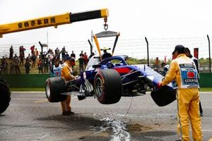 Marshals remove the damaged car of Alexander Albon, Toro Rosso STR14, from the circuit after his crash during practice 3